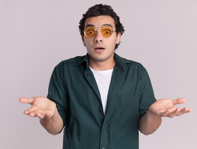 Młody mężczyzna w zielonej koszuli w okularach patrząc na przód zaskoczony i zdezorientowany z podniesionymi rękami stojąc na białej ścianie