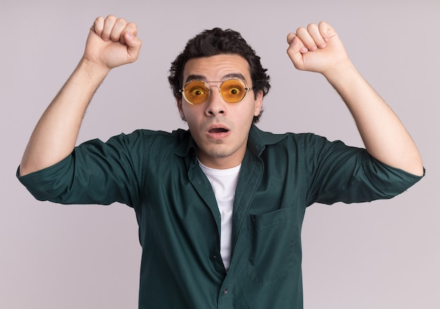 Młody mężczyzna w zielonej koszuli w okularach patrząc z przodu zaskoczony i zdumiony podnosząc pięści stojąc nad białą ścianą