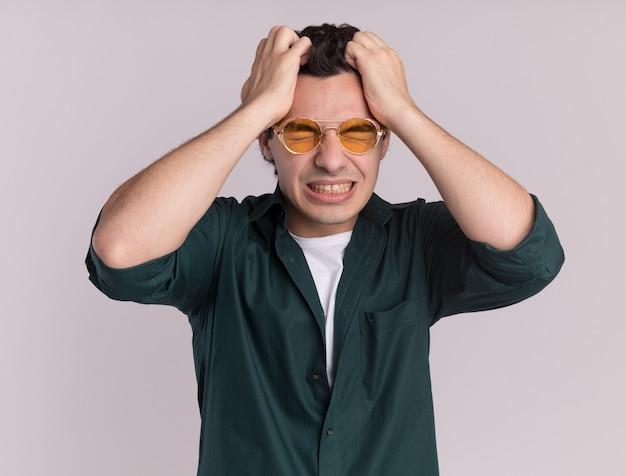 Młody mężczyzna w zielonej koszuli w okularach szaleje, ciągnąc za włosy stojąc na białej ścianie
