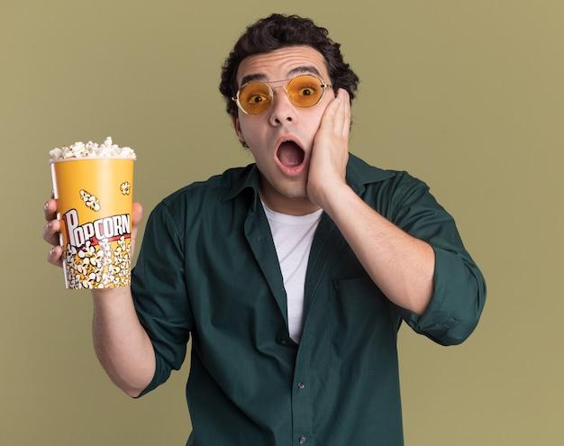 Młody mężczyzna w zielonej koszuli w okularach trzyma wiadro z popcornem patrząc na przód zdumiony i zaskoczony stojąc nad zieloną ścianą