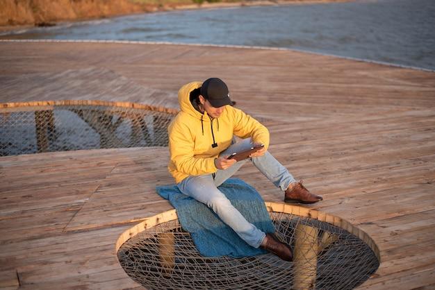 Młody mężczyzna w żółtej wiatrówce i czarnej czapce siedzi na drewnianym molo