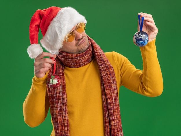 Młody mężczyzna w żółtym golfie i czapce świętego mikołaja w okularach trzymający zabawki na choinkę patrząc na nie ze zdezorientowanym wyrazem twarzy mającym wątpliwości stojąc nad zieloną ścianą