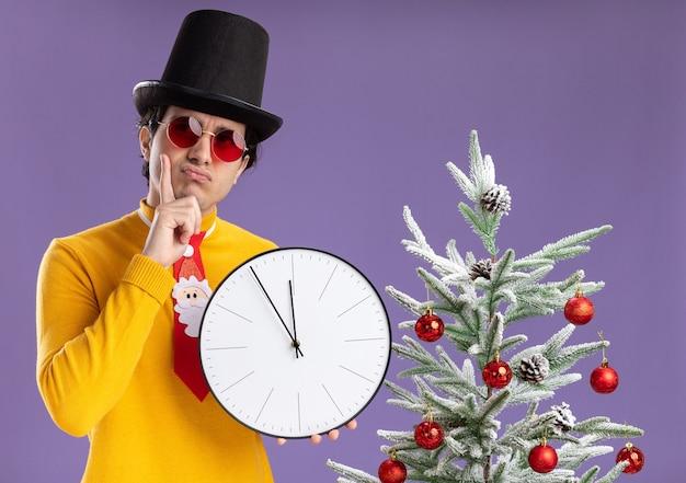 Młody mężczyzna w żółtym golfie i okularach ubrany w czarny kapelusz trzymający zegar ścienny patrzący na bok zdziwiony stojący obok choinki na fioletowym tle