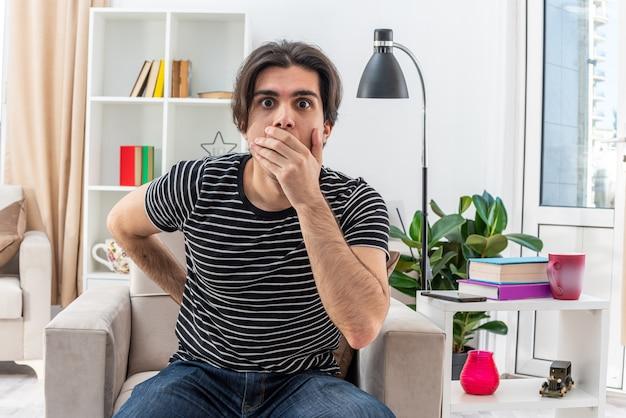 Młody mężczyzna w zwykłych ubraniach jest zszokowany zakrywając usta ręką siedzącą na krześle w jasnym salonie living