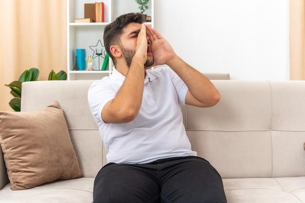 Młody mężczyzna w zwykłych ubraniach krzyczy lub dzwoni rękami przy ustach, siedząc na kanapie w jasnym salonie