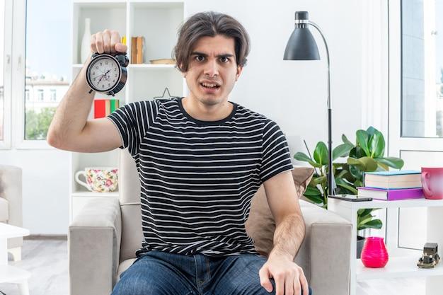 Młody mężczyzna w zwykłych ubraniach pokazujący budzik zdezorientowany i niezadowolony, siedzący na krześle w jasnym salonie