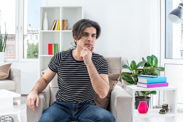 Młody mężczyzna w zwykłych ubraniach siedzący na krześle z zamyślonym wyrazem twarzy z ręką na brodzie w jasnym salonie