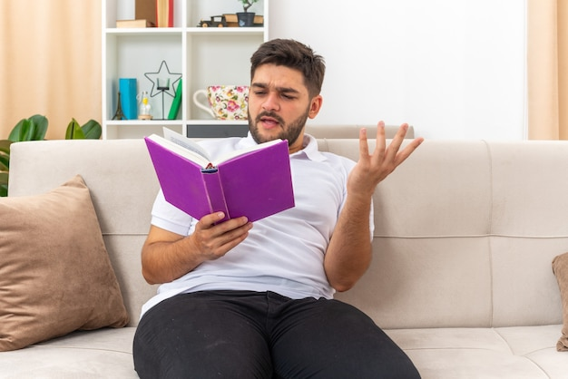 Młody mężczyzna w zwykłych ubraniach, trzymający czytanie książki z mylącym wyrazem, siedzący na kanapie w jasnym salonie