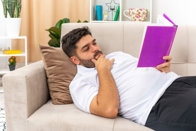 Młody mężczyzna w zwykłych ubraniach, trzymający czytanie książki z poważną twarzą, spędzający weekend w domu leżąc na kanapie w jasnym salonie