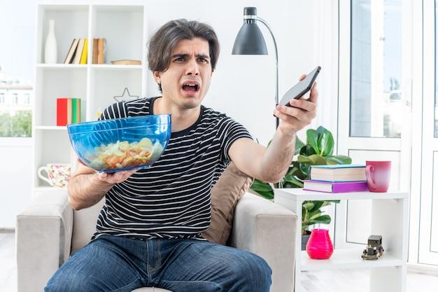 Młody mężczyzna w zwykłych ubraniach, trzymający miskę chipsów i smartfona, patrzący na bok zdezorientowany i niezadowolony, siedzący na krześle w jasnym salonie living