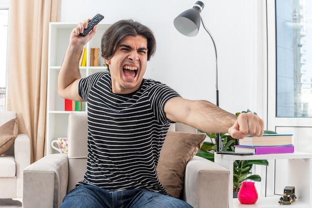 Młody mężczyzna w zwykłych ubraniach, trzymający pilota od telewizora, krzyczący, szalejący, siedzący na krześle w jasnym salonie