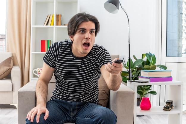 Młody mężczyzna w zwykłych ubraniach, trzymający pilota telewizora, wyglądający na zdziwionego i zdziwionego, siedzącego na krześle w jasnym salonie living