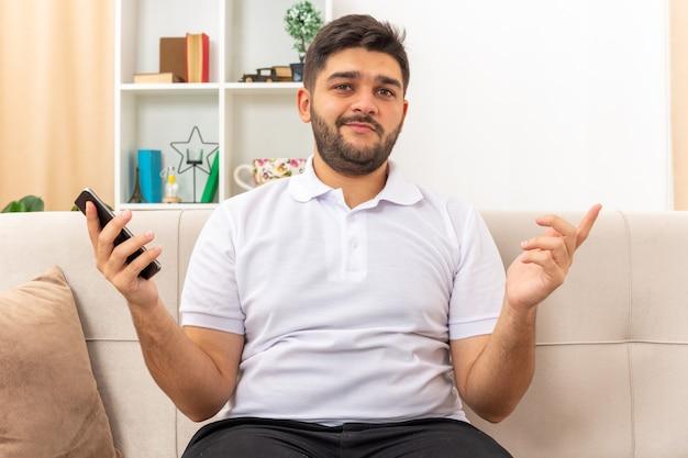 Młody mężczyzna w zwykłych ubraniach, trzymający smartfona, wyglądający na szczęśliwego i zadowolonego, siedzącego na kanapie w jasnym salonie