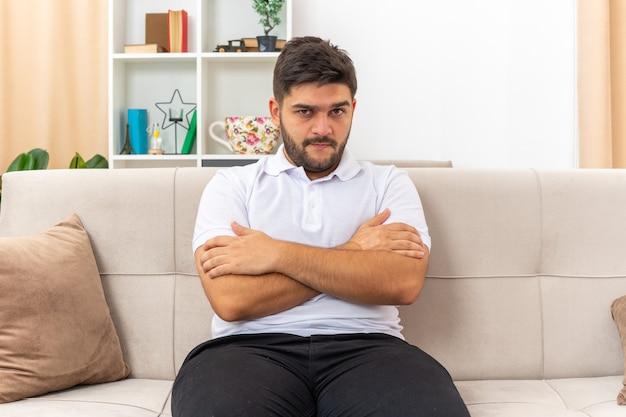 Młody mężczyzna w zwykłych ubraniach wyglądający na obrażonego ze skrzyżowanymi rękami, siedzący na kanapie w jasnym salonie