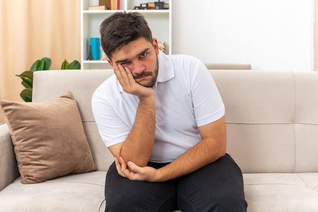 Młody mężczyzna w zwykłych ubraniach wyglądający na przygnębionego z ręką na brodzie, siedzący na kanapie w jasnym salonie