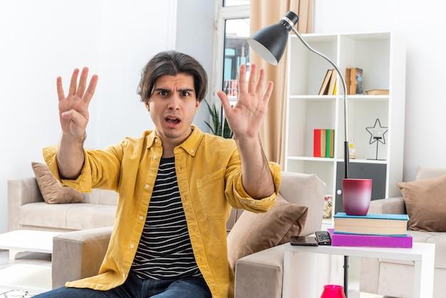 Młody mężczyzna w zwykłych ubraniach wyglądający na zaskoczonego pokazujący numer dziewięć z palcami siedzącymi na krześle w jasnym salonie