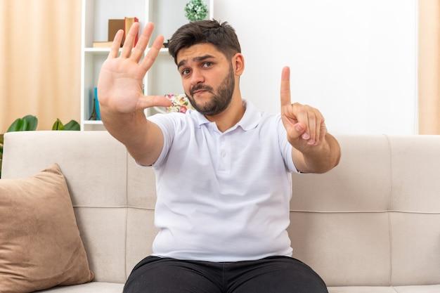 Młody mężczyzna w zwykłych ubraniach wyglądający na zdezorientowanego i niezadowolonego pokazujący numer sześć siedzący na kanapie w jasnym salonie