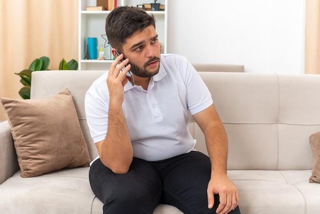 Młody mężczyzna w zwykłych ubraniach wyglądający na zdezorientowanego podczas rozmowy przez telefon komórkowy, siedzący na kanapie w jasnym salonie