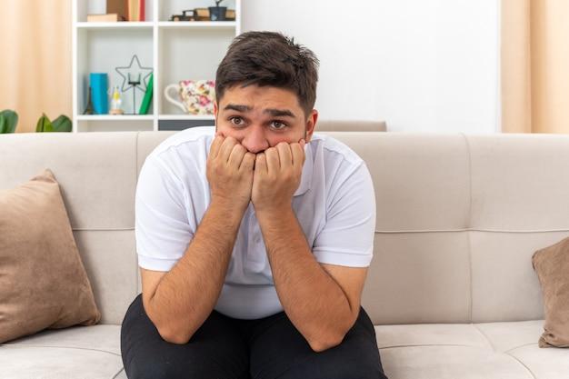 Młody mężczyzna w zwykłych ubraniach wyglądający na zestresowanego i nerwowego obgryzającego paznokcie siedzący na kanapie w jasnym salonie