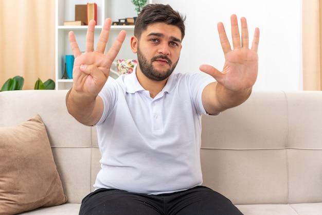 Młody mężczyzna w zwykłych ubraniach z poważną twarzą pokazujący numer dziewięć, siedzący na kanapie w jasnym salonie