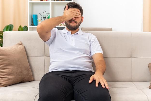 Młody mężczyzna w zwykłych ubraniach zmęczony i znudzony zakrywający oczy ręką siedzącą na kanapie w jasnym salonie living