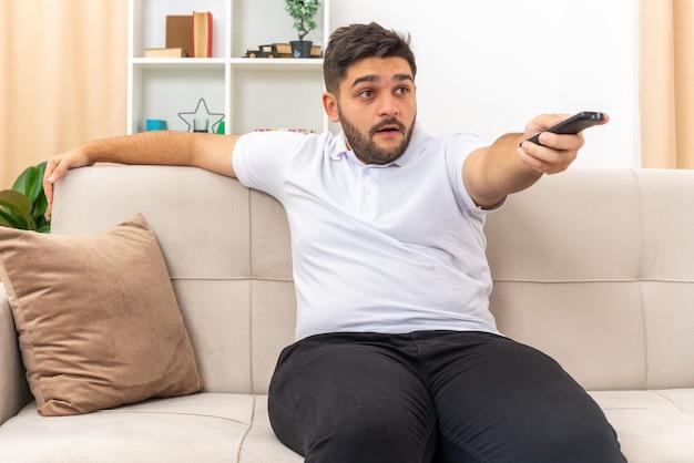 Młody mężczyzna w zwykłym ubraniu trzymający pilota do telewizora wyglądający na zaintrygowanego oglądającego telewizję spędzający weekend w domu, siedząc na kanapie w jasnym salonie