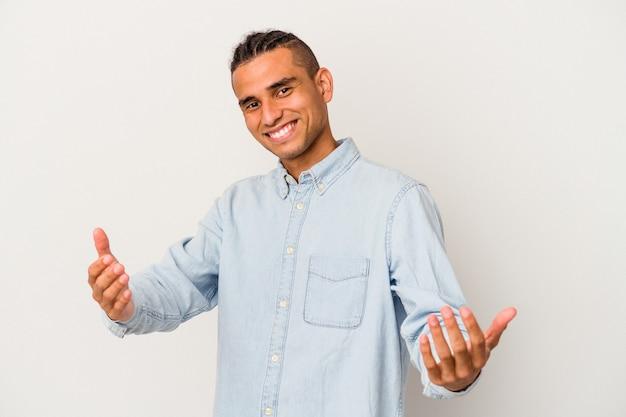 Młody mężczyzna wenezuelski na białym tle pokazując powitalny wyraz.