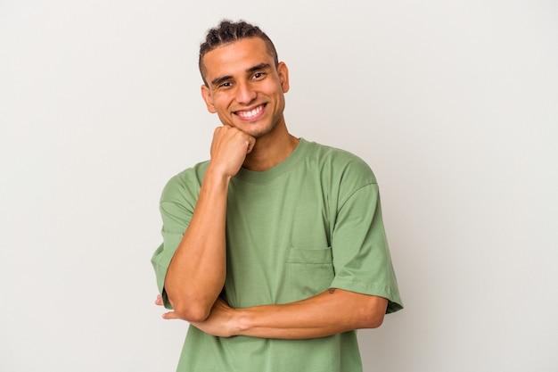 Młody mężczyzna wenezuelski na białym tle uśmiechnięty szczęśliwy i pewny siebie, dotykając podbródka ręką.