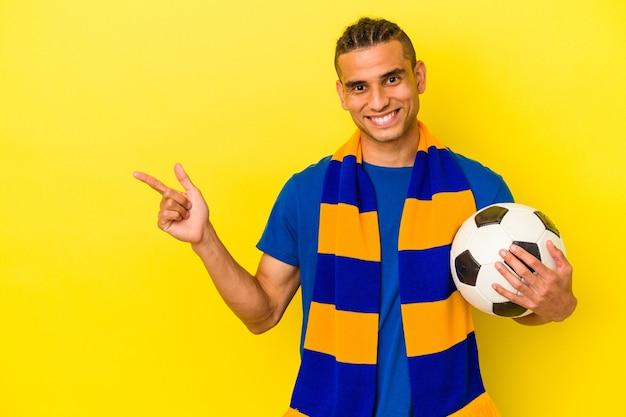 Młody mężczyzna wenezuelski ogląda piłkę nożną na białym tle na żółtym tle, uśmiechając się i wskazując na bok, pokazując coś w pustej przestrzeni.
