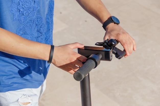Młody mężczyzna włącza skuter elektryczny z bliska