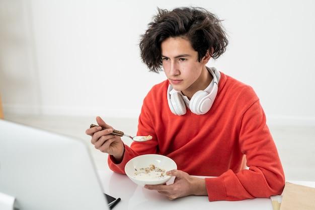 Młody mężczyzna wolny strzelec mający musli z mlekiem, siedząc przy biurku przed monitorem komputera i oglądając wideo