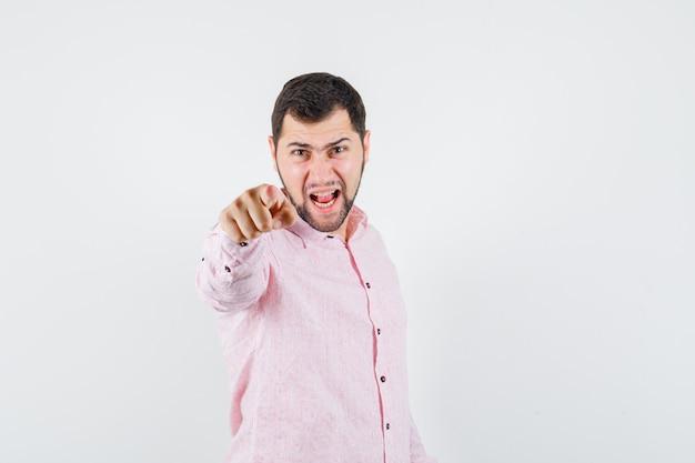 Młody mężczyzna, wskazując na aparat, krzycząc w różowej koszuli i patrząc nerwowo