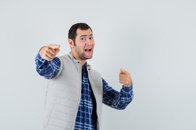 Młody mężczyzna, wskazując na aparat w koszuli, kurtce bez rękawów i patrząc wesoło, widok z przodu.