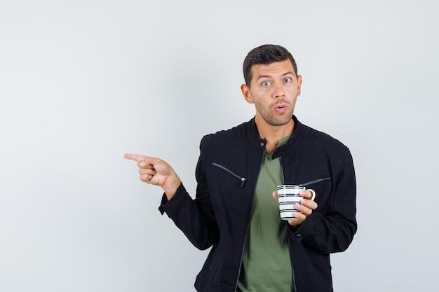 Młody mężczyzna wskazując na bok trzymając kubek w koszulce, kurtce i patrząc zdziwiony, widok z przodu.