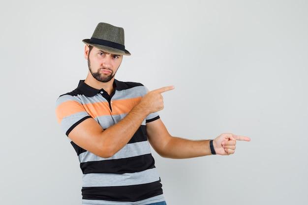 Młody mężczyzna, wskazując na bok w koszulce, kapeluszu i patrząc z góry.