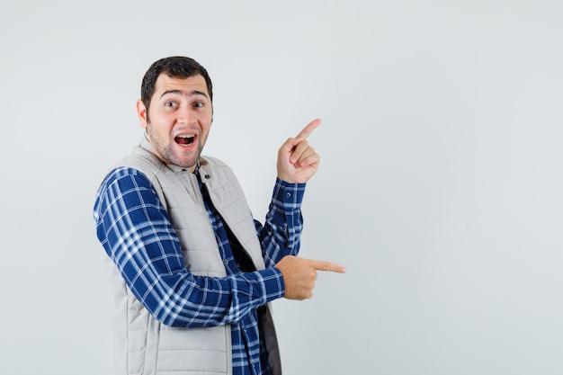 Młody mężczyzna wskazując na bok w koszuli, kurtce bez rękawów i patrząc rozbawiony, widok z przodu. miejsce na tekst