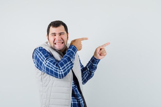 Młody mężczyzna wskazując na bok w koszuli, kurtce bez rękawów i patrząc wesoło. przedni widok.