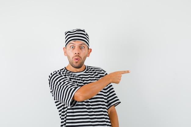 Młody mężczyzna, wskazując na bok w pasiastym t-shirtowym kapeluszu i patrząc przestraszony