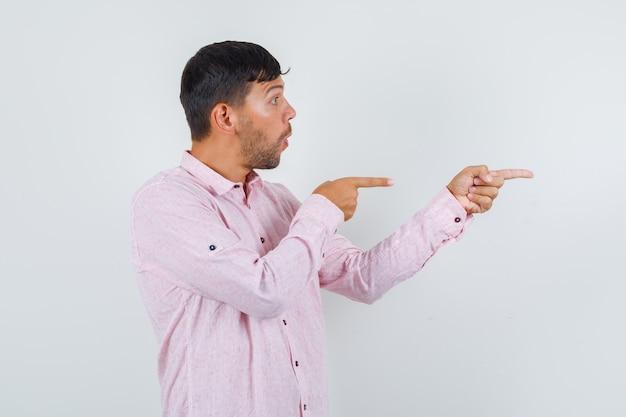 Młody mężczyzna, wskazując na bok w różowej koszuli i wyglądający na zaskoczonego. przedni widok.