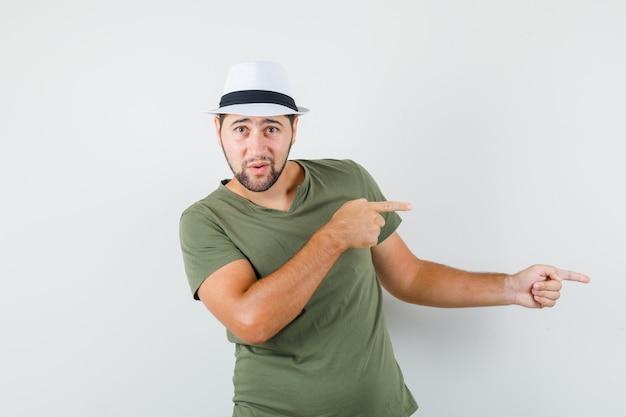 Młody mężczyzna, wskazując na bok w zielonej koszulce i kapeluszu i patrząc niepewnie