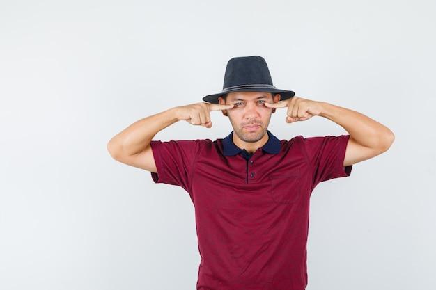 Młody mężczyzna, wskazując na dolną powiekę w koszulce, kapeluszu i patrząc bezsennie, widok z przodu.