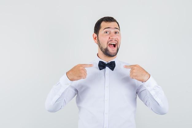 Młody mężczyzna, wskazując na jego muszkę w białej koszuli i wyglądający pewnie. przedni widok.