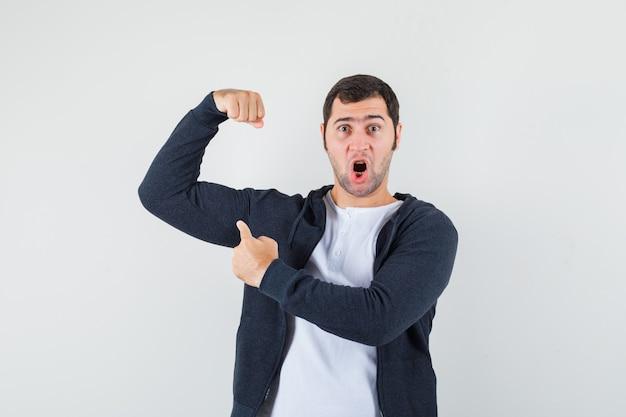 Młody mężczyzna, wskazując na mięśnie ramion w koszulce, kurtce i patrząc potężny, widok z przodu.