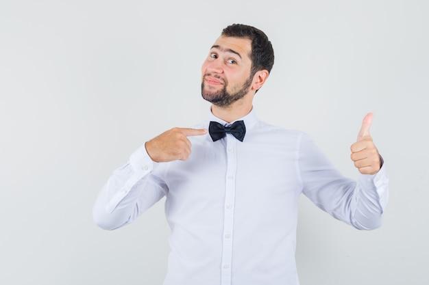 Młody mężczyzna wskazując na swoją muszkę, pokazując kciuk w białej koszuli i patrząc wesoło, widok z przodu.