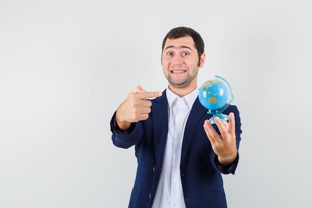 Młody mężczyzna, wskazując na szkolnej kuli ziemskiej w koszuli i kurtce i patrząc wesoło