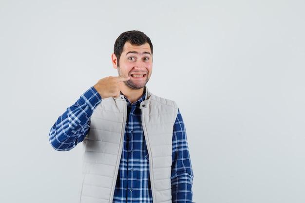 Młody mężczyzna, wskazując na zęby w koszuli, widok z przodu kurtki bez rękawów.