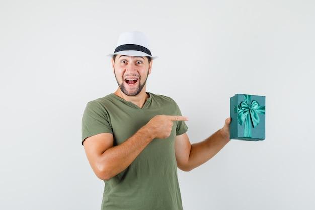 Młody mężczyzna, wskazując obecnie pole w zielonej koszulce, kapeluszu i patrząc szczęśliwy