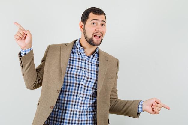 Młody mężczyzna wskazując palcami w górę iw dół w koszuli