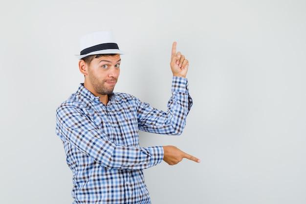 Młody mężczyzna wskazując palcami w górę iw dół w kraciastej koszuli