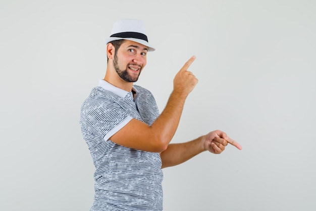 Młody mężczyzna wskazując palce w górę iw dół w koszulce, kapeluszu i patrząc wesoło. przedni widok.